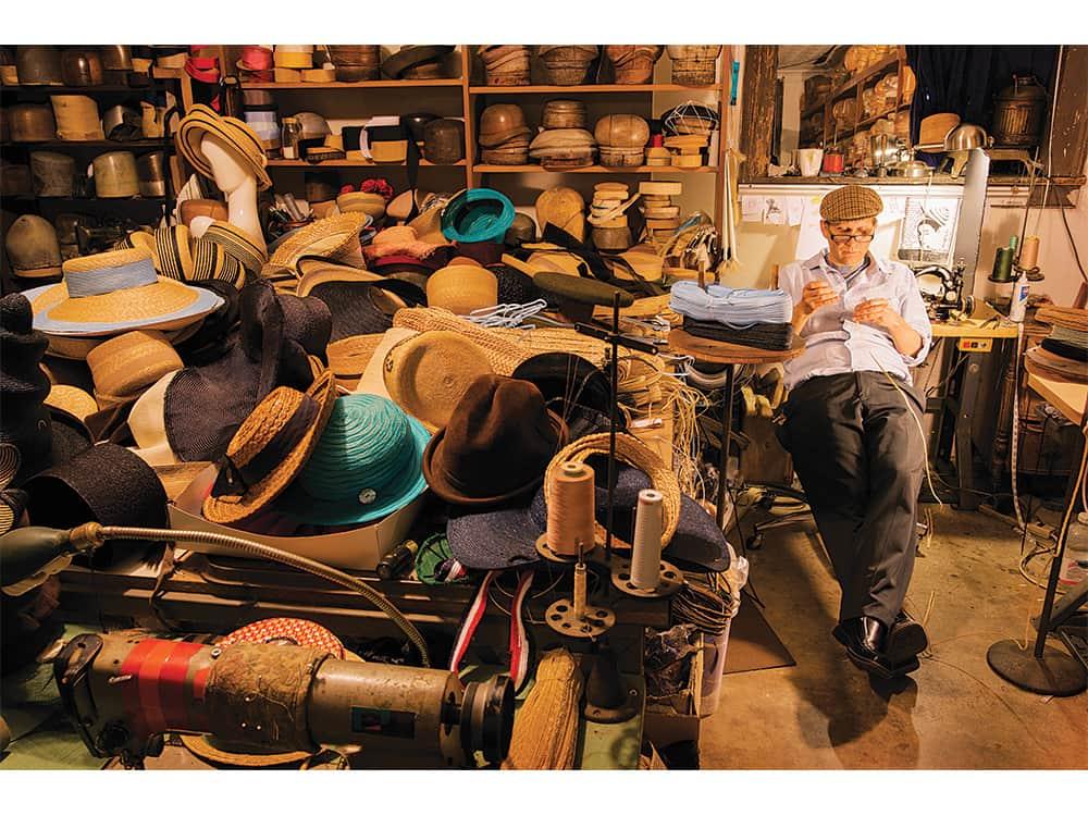Ignatius Hats Creegan at work in his studio filled with hats and hat blocks. Photo: Robert Severi